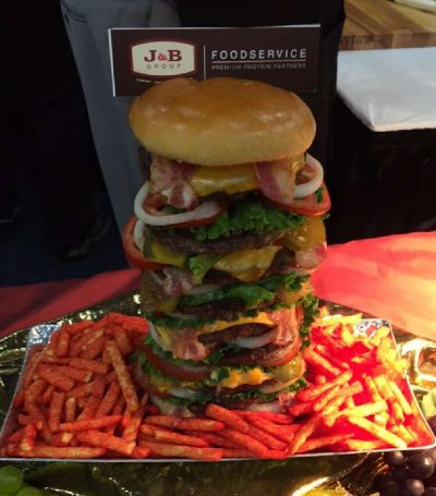 ultra-stuffed bacon cheeseburger surrounded by hot fries prepared by J&B Group